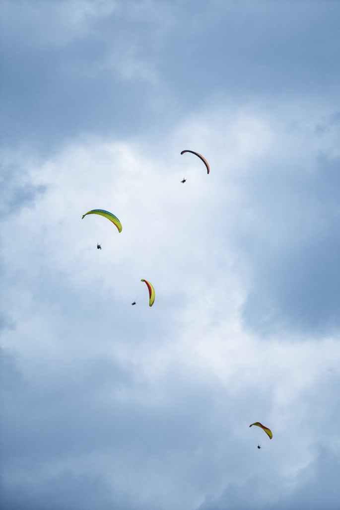 four person parachuting under cloudy sky